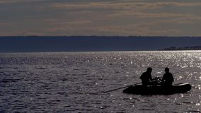 Rubber boat with fishermen silhouette slowly drifts over a large lake. The lake shines in the rays of the evening sun stock footage