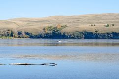 Rubber boat with a motor floats on the river. The hills. Autumn stock images