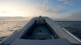 Rubber boat`s bow while drifting in the sunset waters