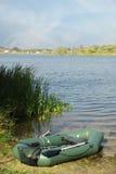 Rubber boot en rivier stock foto