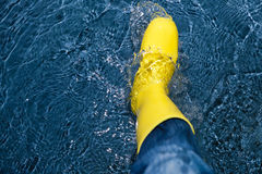 Rubber boot splashing in the water Stock Photos