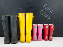 Rubber boots against a blackboard Stock Image