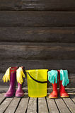 Rubber boots, bucket and gloves on veranda Royalty Free Stock Photos