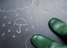 Rubber boots with drawing of rainy day on the blackboard  Stock Images