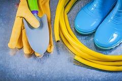 Rubber boots garden hose protective gloves hand spade. On metallic background gardening concept royalty free stock photos