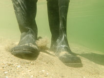 Rubber boots or gumboots underwater on sand ground Stock Photography