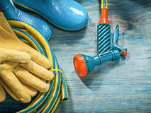 Rubber boots leather protective gloves garden hose pistol on woo Stock Photo