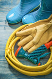 Rubber boots leather protective gloves garden hose on wooden boa. Rd gardening concept stock photography