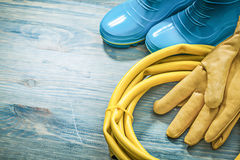 Rubber boots leather safety gloves garden hose on wooden board g. Ardening concept royalty free stock photo