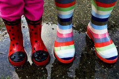 Rubber boots in a rain puddle. Two sets of rubber boots in a puddle of rain water Stock Photo