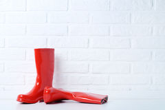Rubber boots. Red rubber boots on brick wall background Stock Images