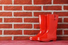 Rubber boots. Red rubber boots on brick wall background Royalty Free Stock Photography