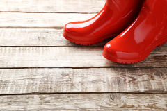 Rubber boots. Red rubber boots on a brown wooden table royalty free stock photography