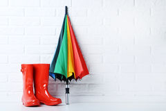 Rubber boots. Red rubber boots with umbrella on brick wall background Royalty Free Stock Images