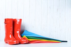 Rubber boots. Red rubber boots with umbrella on wall paneling background Royalty Free Stock Images