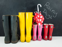 Rubber boots with an umbrella  against a blackboar Stock Photo