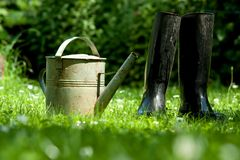 Rubber boots with watering can Royalty Free Stock Photos