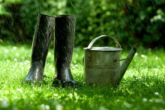 Rubber boots with watering can Stock Images
