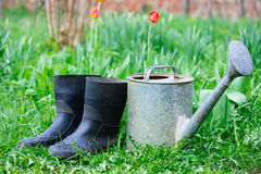 Rubber boots with watering can on grass Royalty Free Stock Image