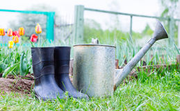 Rubber boots with watering can on grass Stock Photos