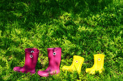 Rubber boots for woman and kid in green summer grass Stock Photography