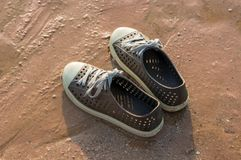 Rubber brown sneakers on beach. Rubber brown sneakers lay on the wet sand of a beach Royalty Free Stock Photos