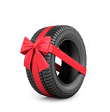 Rubber car tire with red ribbon and bow Stock Image
