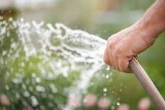 Rubber de slangbuis van het holdingswater watering stock foto