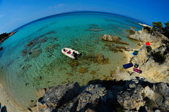 Rubber dinghy. Anchored nearby small  lagoon, hidden among rocks, Sithonia, Greece, fisheye view from above Stock Photo