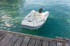 a rubber dinghy tied to a jetty in the tropics Stock Image