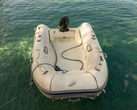 A rubber dinghy tied to a jetty in the tropics Stock Photos