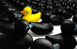 Rubber Duck Against The Flow. A non-conformist depiction of a yellow rubber bath duck swimming against the flow of black rubber ducks Stock Image