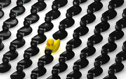 Rubber Duck Against The Flow Grid. A non-conformist depiction of a yellow rubber bath duck swimming against the flow of black rubber ducks Royalty Free Stock Image