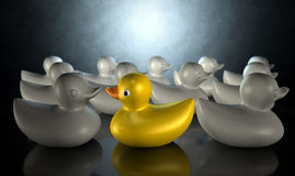 Rubber Duck Against The Flow. A yellow rubber bath duck swimming against the flow of a group of grey rubber ducks on a dark backlit background royalty free illustration