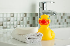 Rubber Duck in Bathroom. Yellow rubber duck on bathroom sink with face cloth and bar of soap Stock Images