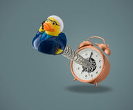 Rubber duck business man coming out of alarm clock Stock Photo