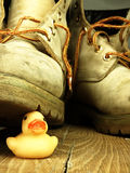 Rubber duck crushed by a heavy, old military boot. Stock Photo