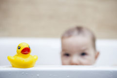 Rubber duck over the bathtube. 9 months baby boy having fun in the bathtub stock images