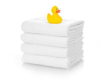 Rubber duck on white towels. Isolated on white royalty free stock images