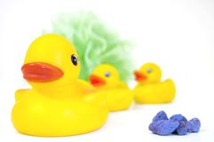 Rubber Ducks and Pumice Stones. A row of yellow rubber ducks, a net sponge and pumice stones for the bath Royalty Free Stock Image
