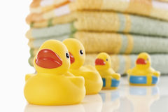 Rubber ducks and stack of colorful towels Stock Photos