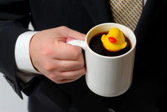 Rubber Ducky in Coffee Cup 2. Yellow rubber ducky floating in a coffee cup being held by a man in a business suit royalty free stock photography