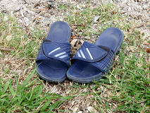Rubber flip flops slide sandals men. On ground Stock Photography