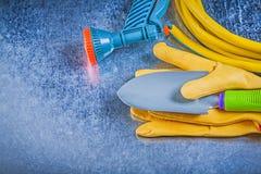 Rubber garden hose spray nozzle protective gloves hand shovel on. Metallic background gardening concept stock photos