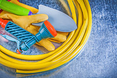 Rubber garden hose spray nozzle safety gloves hand spade on meta. Llic background gardening concept stock images