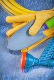 Rubber garden hose water sprayer safety gloves spade on metallic. Background gardening concept stock image