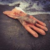 Rubber glove on the beach Stock Photos