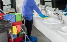 Rubber gloved hand schoonmakende gootsteen met stofdoek stock foto's