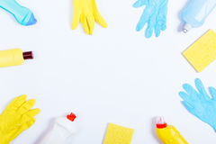 Rubber gloves, sponges and bottles of cleaning fluids on a white Stock Images