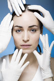 Rubber gloves touching womans face Stock Image